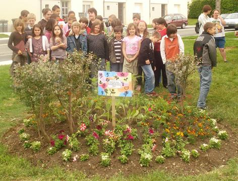 Photo des élèves avec un massif de fleurs au premier plan