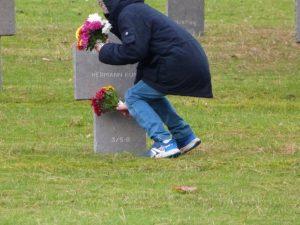 Un enfant dépose des fleurs au cimetière militaire Dormans 11 novembre 2016
